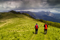 Two hikers on green mountain meadow. Two hikers trekking over  green meadow surrounder by the  high mountains Stock Photography