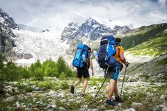 Two hikers with large backpacks in mountains. Tourists hike on rocky mounts. Leisure activity on mountain trek. Adventure of men in wild Svaneti region of stock photos