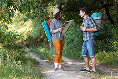 Two Hikers looking Map staying on Forest Trail Stock Photos