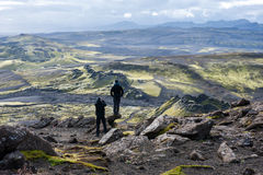Two hikers looking at volcanic landscape in Lakagigar, Laki craters, Iceland. Two hikers looking at volcanic landscape in Lakagigar, Laki craters, Central Royalty Free Stock Photo