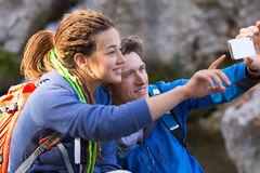 Two Hikers Man and Girl taking Photo with Mobile Telephone. Two Hikers Man and Girl with Dreadlocks Hair Style smiling taking self Portrait Photo with Camera of Stock Images