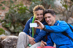 Two Hikers Man and Girl taking Photo with Mobile Telephone. Two Hikers Handsome Man Cute Girl with Dreadlocks Hair Style smiling taking self Portrait with Camera Stock Photo
