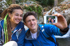 Two Hikers Man and Girl taking Photo with Mobile Telephone. Two Hikers Handsome Man and Cute Girl with Dreadlocks Hair Style smiling taking self Portrait Photo Royalty Free Stock Photography