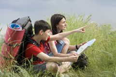 Two hikers with the map Stock Photos