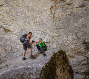 Two hikers on a mountain cliff Stock Photos