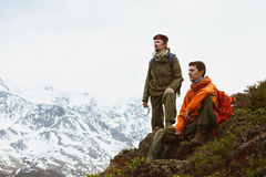Two hikers mountain slope glacier. Two hikers having rest on mountain slope on background of glacier. Space for text Stock Images