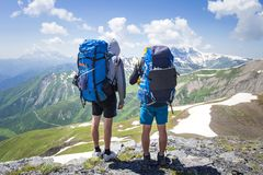 Two hikers in mountains with backpacks on sunny summer day. Mountain trek in Svaneti, Georgia. Tourists on peak of highland look at snowy mountains on blue sky royalty free stock photography