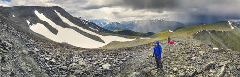 Two hikers in mountains. Two hikers walk along a range in the altai mountains Royalty Free Stock Photography