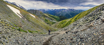 Two hikers in mountains. Two hikers walk along a range in the altai mountains Stock Image