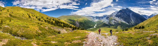 Two hikers in mountains. Two hikers walk along a trail in the altai mountains Stock Photos