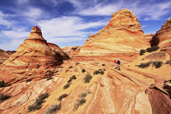 Two Hikers Outside The Wave. Two hikers marvel at the petrified sandstone formations, right outside The Wave in the Coyote Buttes section of the Paria Canyon Stock Photos
