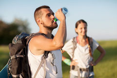 Two hikers. Portrait of a happy young couple. Man drink water from waterbottle standing outdoors, women stands behind Stock Photography