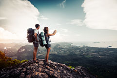 Two hikers relax on top of a mountain Stock Images
