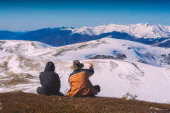 Two hikers sit on a hill and enjoy the mountain valley Stock Photo