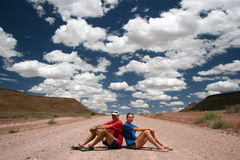 Two hikers sitting on gravel road Royalty Free Stock Photo