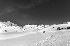 Two hikers on snow plateau (black and white) Stock Photo