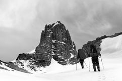 Two hikers in snowy mountains before storm. Turkey, Central Taurus Mountains, Aladaglar, plateau Edigel Yedi Goller. Black and white toned landscape Royalty Free Stock Photo