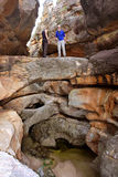 Two hikers stand on natural bridge Royalty Free Stock Image