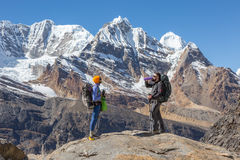 Two Hikers staying on top of Rock and relaxing. Overlooking surrounding high Mountains Scenery having refreshment drinking Water from Flask Stock Photography