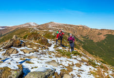 Two Hikers staying on winter Mountain terrain pointing. Observing Landscape Snow and grassy Trail Backpacks and walking Poles Royalty Free Stock Photos