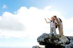 Two hikers at the summit. Happy female hikers point at the view while standing on top of a rock stock photo