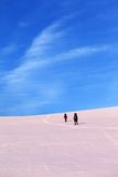 Two hikers on sunrise snow plateau Royalty Free Stock Photography