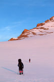 Two hikers in sunrise snowy plateau Stock Photo
