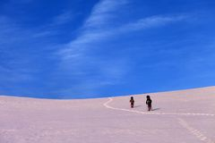 Two hikers on sunrise snowy plateau Royalty Free Stock Image