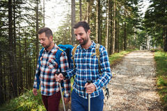 Two hikers talking together on a trail in the woods Stock Photo