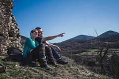 Two hikers on top of the mountain enjoying sun over the valley. stock photo