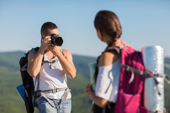 Two hikers. Two tourists. Man photographs woman, she is holding a map Stock Photography