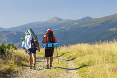 Two hikers tourists on a path in mountains.  Royalty Free Stock Image