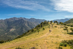 Two hikers on trail near Novella in Balagne region of Corsica. Two female walkers on a track near Novella in the Balagne region of north Corsica with the village Stock Image