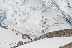Two Hikers View Mount Rainier Glaciers. From rocky mountain top Royalty Free Stock Images