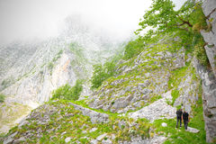 Two hikers viewed from behind while they return to where they started after visiting the areas of extraction of marble Stock Image