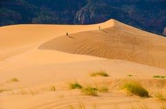 Two hikers walk the rim of tall sand dunes in Utah Stock Photo