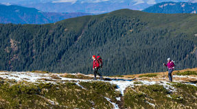 Two Hikers walking along Mountain ridge. Two Hikers walking along Mountain Crest Bright Colors sporty Clothing Backpacks and trekking Poles Hills covered by Royalty Free Stock Photos