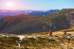 Two Hikers walking along Mountain ridge with Sun shining. Two Hikers walking along Mountain Crest Bright Colors sporty Clothing Backpacks and trekking Poles Stock Photo