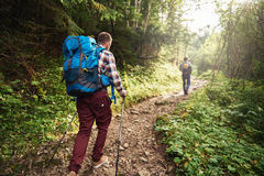 Two hikers walking along a trail deep in the forest Stock Photography