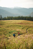 Two hikers walking down a trail together in the mountains Stock Photos