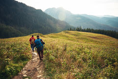 Two hikers walking down a trail in the wilderness Stock Photo