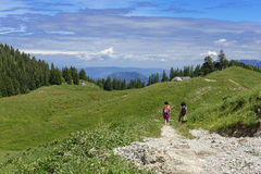 Two hikers walking in the mountains Stock Photos