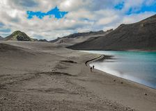 Two hikers walking on the shoreline of lake Langisjor royalty free stock images