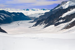 Two Hikers Walking Towards the Aletsch Glacier. This is a top view of the Aletsch Glacier photographed from the Jungfraujoch located at 3471 meters in the Stock Image