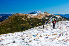 Two Hikers walking up on Snow Slope Mountains View. Two Hikers Man and Woman with Backpacks walking up on Snow Slope Mountains View blue Sky sunny Day Royalty Free Stock Photo