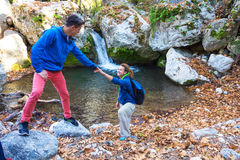 Two Hikers young Man and Smiling Woman holding hands. Helping each other walking mountain stream with waterfall Royalty Free Stock Photo