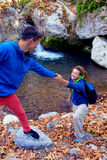Two Hikers young Man and Smiling Woman holding hands vertical. Two Hikers young Man and Smiling Woman holding hands helping each other walking mountain stream Royalty Free Stock Photography