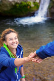 Two Hikers young Man and Smiling Woman holding hands vertical. Two Hikers young Man and Smiling Woman holding hands helping each other walking mountain stream Royalty Free Stock Image