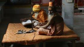 Two hindu men praying at the street in Varanasi. stock footage