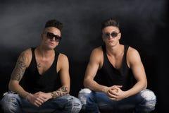 Two hip trendy male friends in studio shot Stock Photo